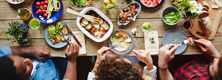 Freunde Essen zusammen, Bunte Salate stehen auf dem Tisch, Man sieht Freunde beim Essen